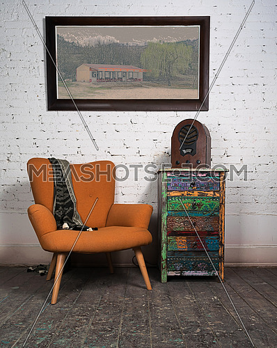 Composition of vintage orange armchair, colorful cupboard, aged wooden radio and hanged painting