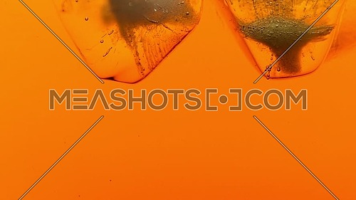 Clear ice cubes with air bubbles float, shake and melt down in cold iced black tea or whiskey, extreme close up, low angle side view, slow motion
