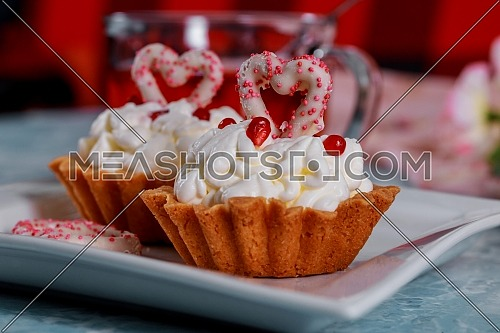Happy Valentine's Day is written on a decorative cupcakes with mascarpone cream. Valentine's day concept