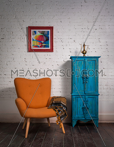 Living room corner with vintage orange armchair and ornate scarf beside blue cupboard on a red carpet, grunge dark wooden parquet floor and white bricks wall