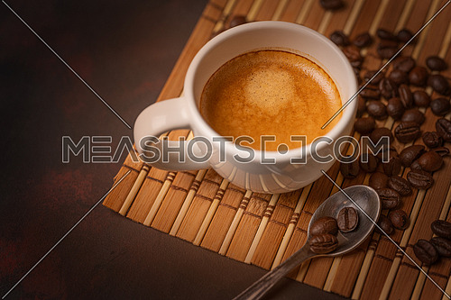 White cup of coffee,teaspoon and coffee bean on dark background. Copy space. Top view.