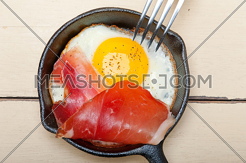 fried egg sunny side up with Italian tyrolean speck smoked ham on a skillet