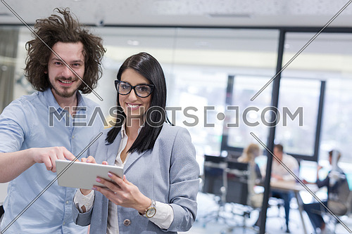 business people using tablet  computer while preparing for next meeting colleagues in the background discussing ideas  at startup office