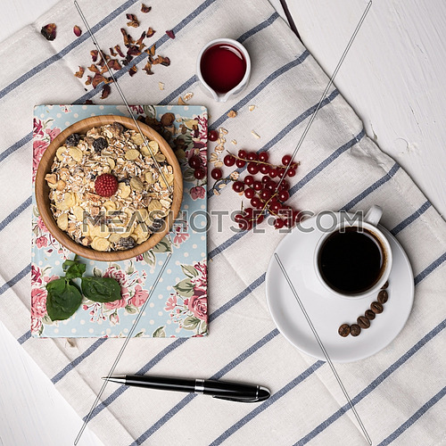 Healthy breakfast with muesli, raspberry, cherries and coffee on a background of white tablecloth, block note, and black pen