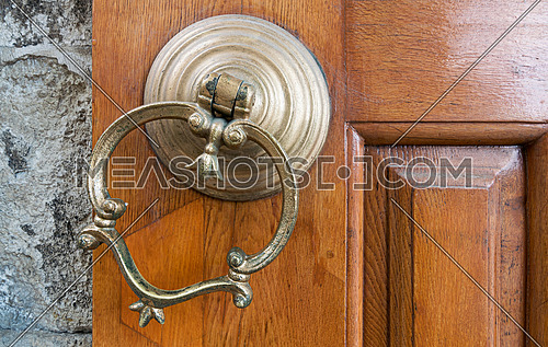 Closeup of antique copper ornate door knocker over an aged wooden door, Eyup Sultan Mosque, Istanbul, Turkey