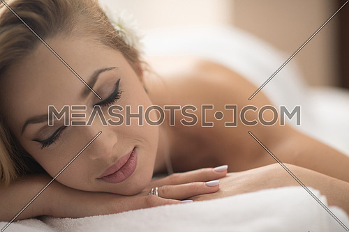 beautiful young woman getting back massage in spa and wellness salon