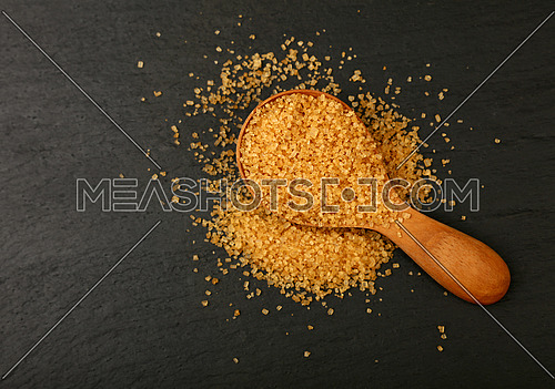 Close up one wooden scoop spoon full of brown cane sugar on black slate board, elevated top view, directly above