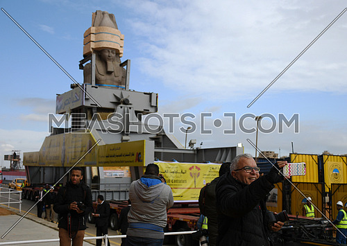 Long shot for The Statue of King Ramses II in the transferring machine at arrival time at the Grand Egyptian Museum in Cairo while a male taking selfie with the statue on 25 January 2018