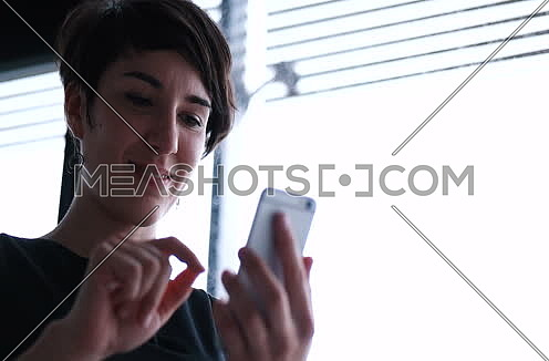 businesswoman using cell phone in modern office by the window