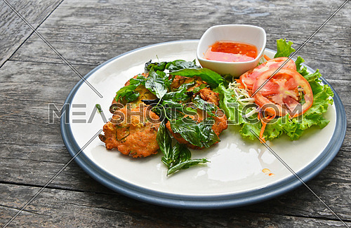 Plate of fish and shrimp deep fried cakes croquettes snack with salad basil leaves and hot sauce on vintage wooden table surface