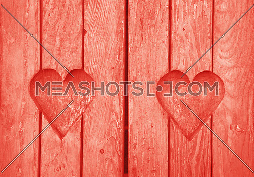 Close up two heart shaped elements, symbol of love, romance and togetherness, wood carved cut in wooden planks texture background, coral pink painted window shutter