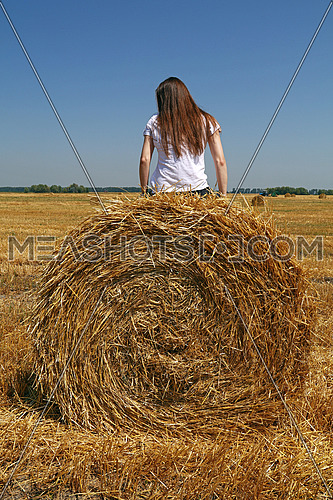 Young Caucasian woman sitting on the straw bale in stubble field after harvesting, low angle rear view
