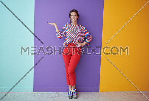 Portrait of happy smiling young beautiful woman in a presenting gesture with open palm isolated on colorful background. Female model in modern fashionable clothes posing in the studio
