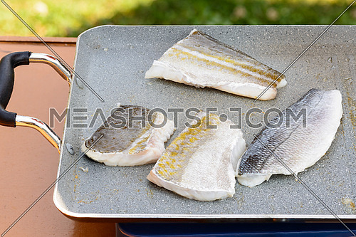 Pictured three fillets of sea bream and codfish cooked on the grill outdoor.