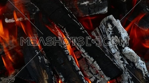 Blaze of bonfire, wood fire flame heat spires burning in fireplace with smoke and trembling in the wind and hot air flow, close up.