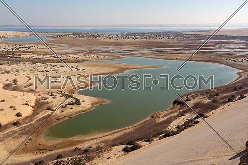 Landscape Arial view of green water lake in sand desert with day light blue sky in landmark Fayoum nature reserve , Egypt