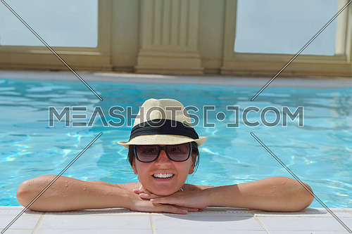 Happy smiling woman with hat and sunglasses  in swimming pool at tropical resort