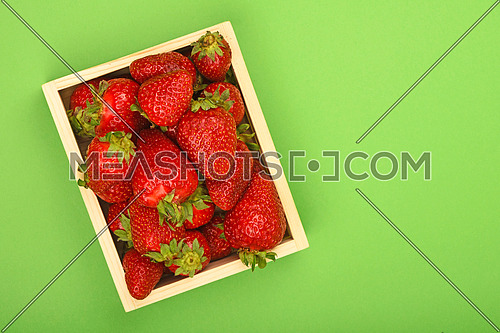 Mellow fresh red summer strawberries in wooden tray box over green paper background, top view