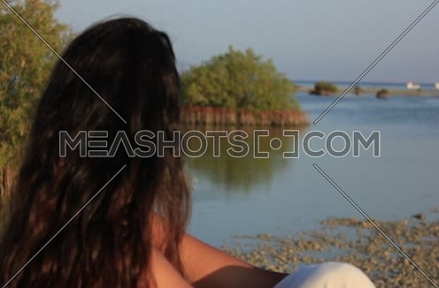 Mid shot for a girl setting on the sea shore looking towards an Island with green trees at wadi Lahmi at day - 5D