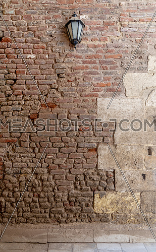 Front view of grunge weathered uneven red stone bricks wall and one lantern, Medieval Cairo, Egypt