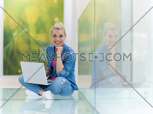 beautiful young woman using laptop computer on the floor at home
