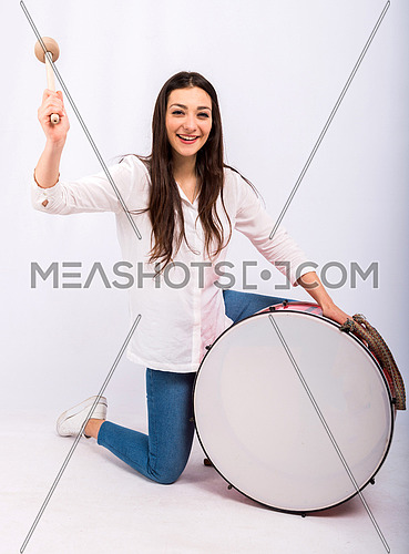 A beautiful young woman playing a drum