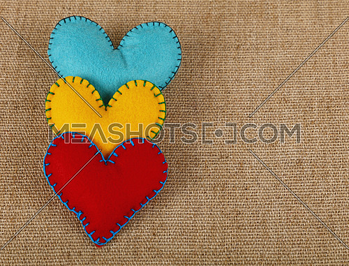 Felt craft and art, three handmade stitched toy hearts, yellow, red and blue on canvas background, close up, elevated high angle view