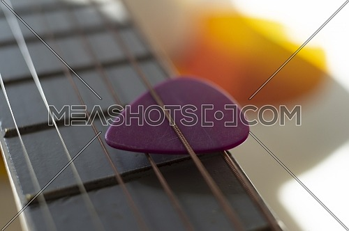 Colorful pink plectrum in guitar strings in a close up oblique angle view in a music and entertainment concept