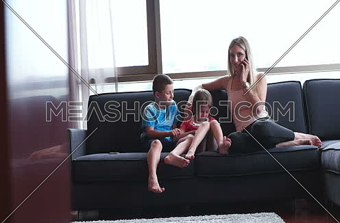 mother using smartphone with kids on sofa in modern apartment
