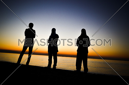 three friends standing together by at the beach during sunset magic hour