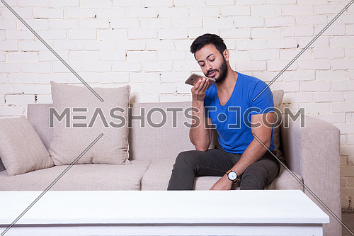A young man sitting on a sofa using his Mobile Phone behind a white wooden table
