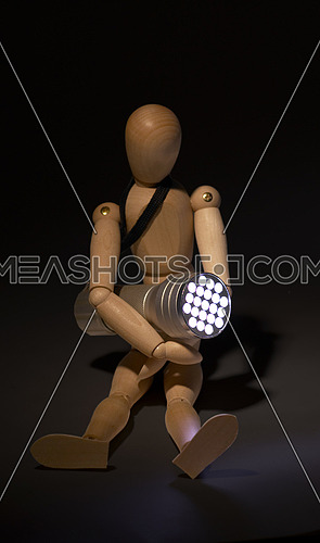 wood mannequin and flashlight glowing on the dark over black background