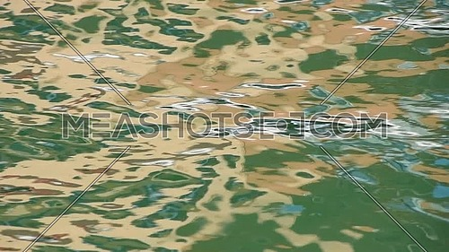 Close up abstract multicolor background of green and yellow reflections on water waves and ripples running at sea surface