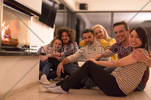 group of young multiethnic couples sitting on the floor in front of fireplace at cold winter night