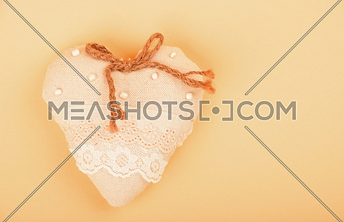 Valentine template, handmade beige toy textile lace heart with burlap jute bow, beads and copy space on paper background