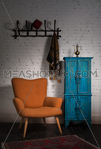 Front view of vintage orange armchair, blue cupboard, wall hanger with ornate scarf and red fez in studio