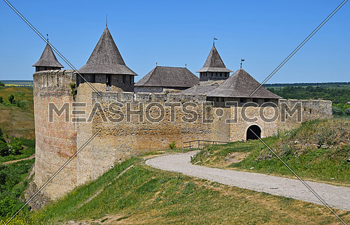 Medieval old fortress castle with ancient stone walls, wooden roofs and road, green hills and clear blue sky, Khotyn, Ukraine