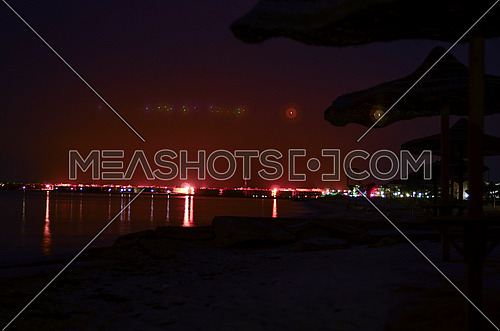 Long exposure view of the beach with lined hay sunshades and the city appears at the far end