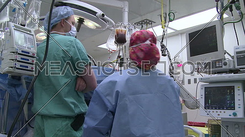 Pan left of medical staff checking equipment during surgery