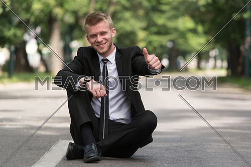 Happy Businessman Sitting on Asphalt Outdoors In Park And Showing Thumbs-Up Sign