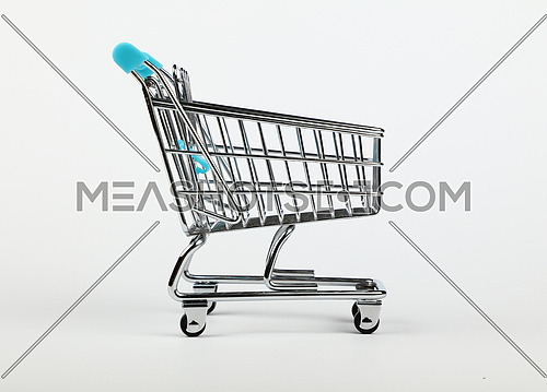 Close up empty toy metal supermarket shopping cart over grey white background, low angle side view