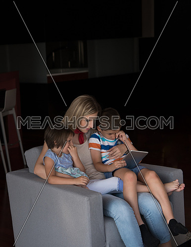 happy Mother spending time with kids using tablet computer on an armchair  at home