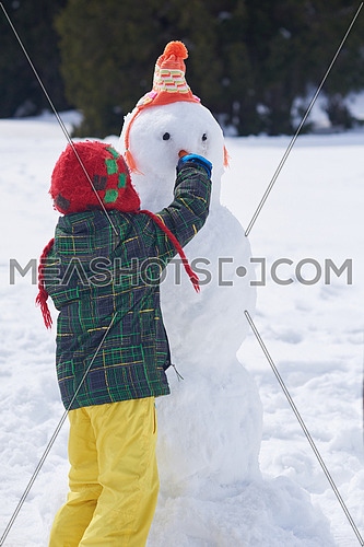 little boy making snowman