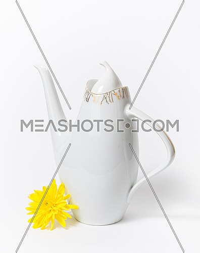 Czech ceramic white teapot and a yellow flower on white background, dating back to the 1960s