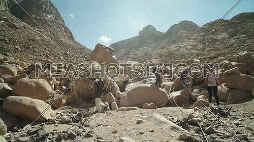 Track out shot for group of tourists go down on big rocks with bedouin guide to explore Sinai Mountain for wadi Freij at day.