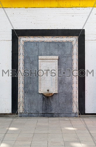 Old white marble water fountain surrounded by an ornate marble frame and black frame over white painted wall