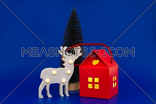 Stylized wooden reindeer house shaped gift box with yellow glowing windows and Christmas tree on a festive blue background. New Year and Christmas holiday season concept card decoration
