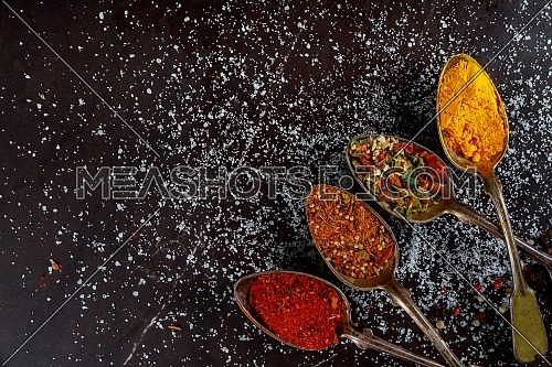 Delicious assortment of ground spice ingredients on dark wooden background