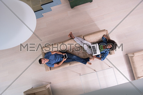 Young multiethnic couple relaxes in the luxury living room, using a tablet and laptop computer top view