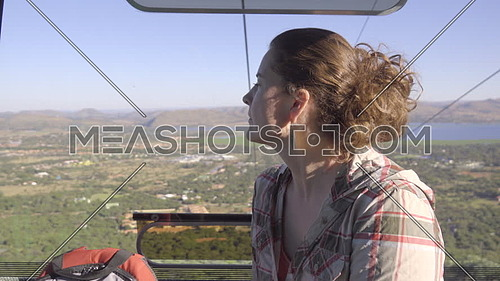 View of tourist looking left from inside cable car